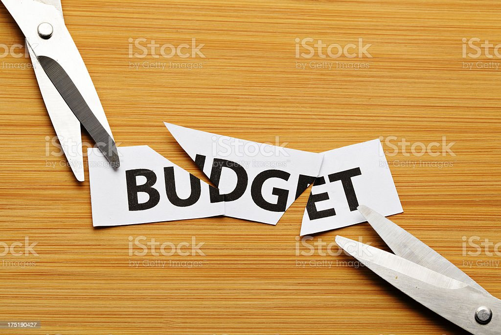 cutting budget with scissor on wooden background stock photo