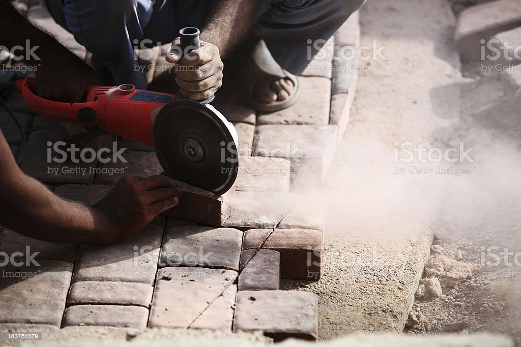 Cutting Concrete Pavement Blocks with Angle Power Disc Grinder stock photo