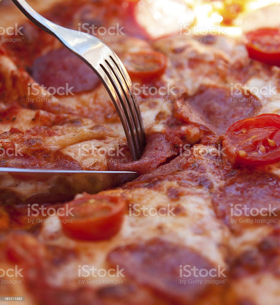 Cutting delicious Italian pizza with help of knife and fork royalty-free stock photo