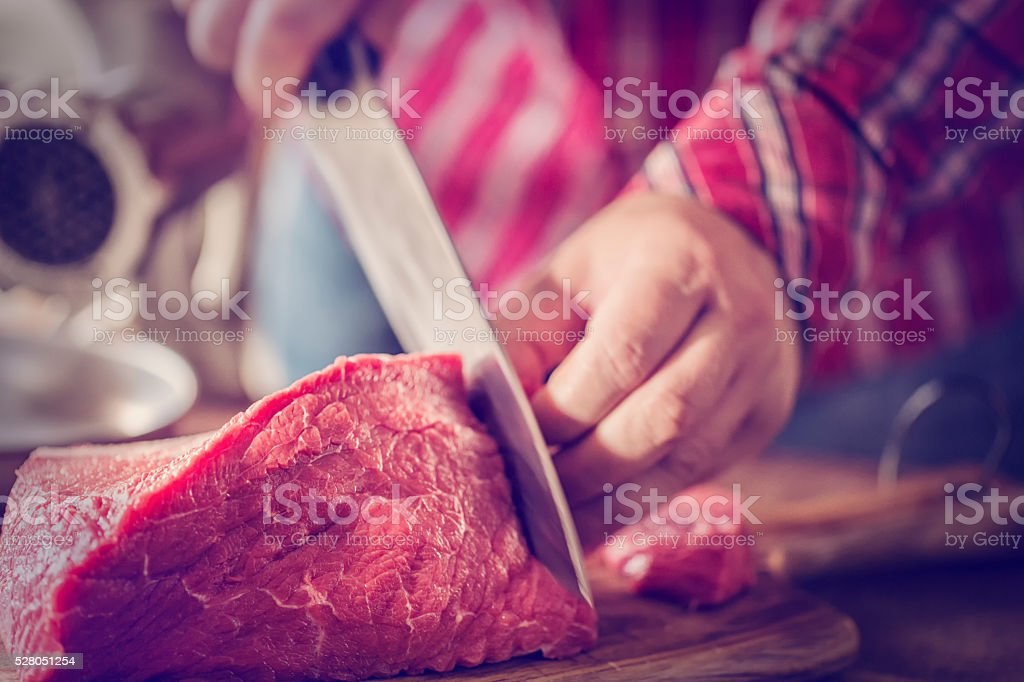 Cutting Fresh Meat to Ground it in a Mincer stock photo