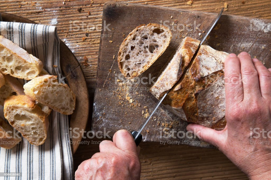Cutting freshly baked bread stock photo
