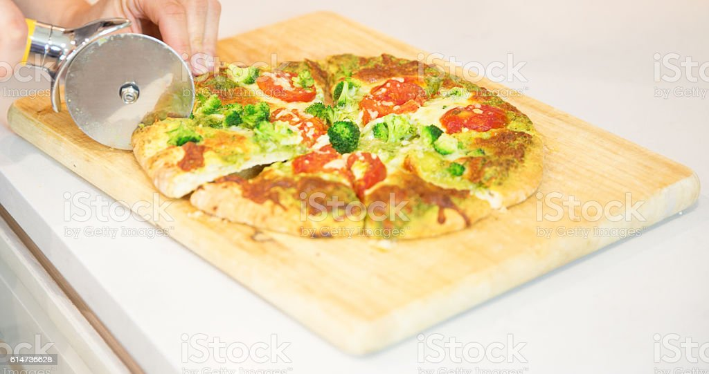 Cutting freshly prepared pizza into pieces stock photo