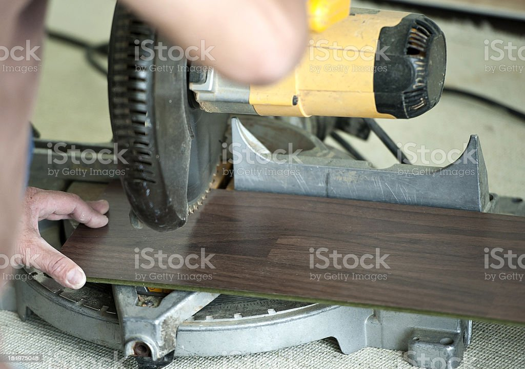 Cutting hardwood floorboard with power saw stock photo