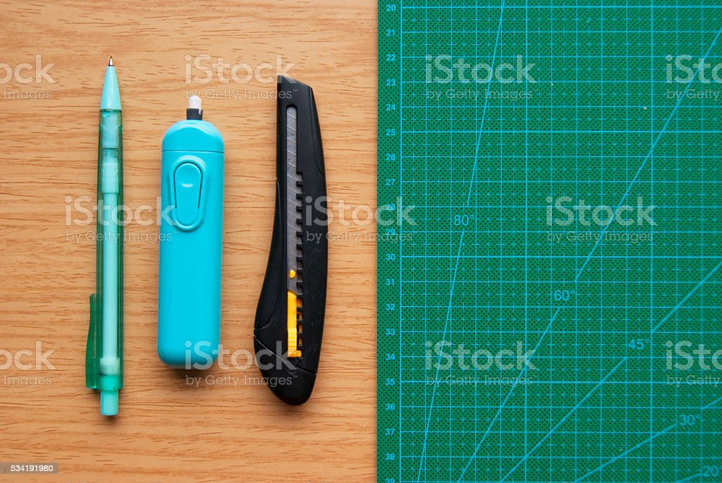 Cutting Mat, Letter Opener, Eraser and Pencil on Wood Desk stock photo