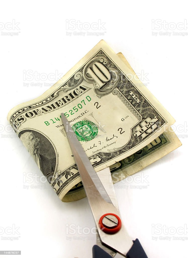 Cutting of money by scissors stock photo