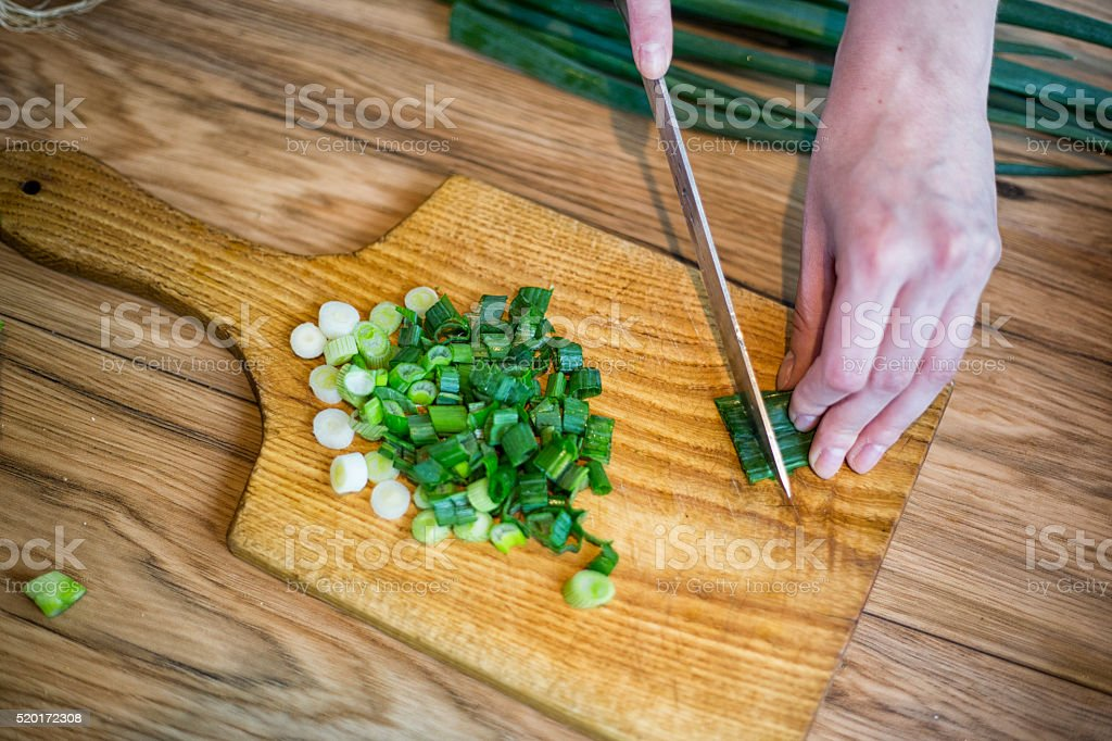 Cutting of spring onions for salad stock photo
