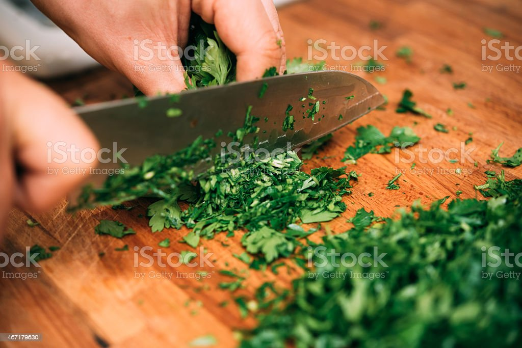 Cutting parsley in a kitchen. stock photo