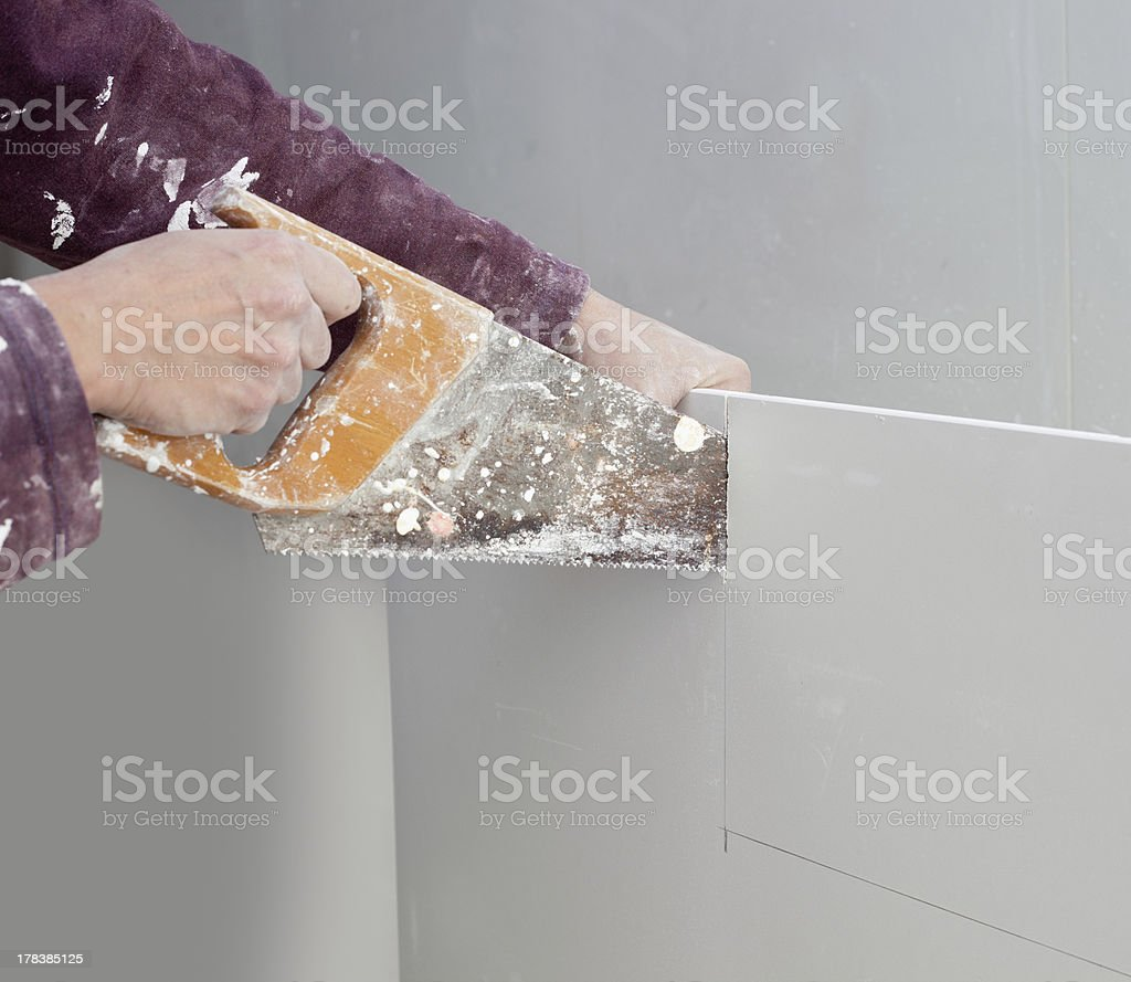 cutting plasterboard plaster hand dirty saw royalty-free stock photo