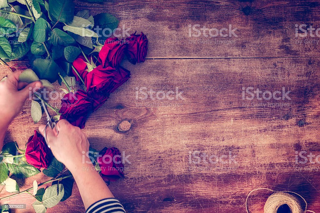 Cutting Romantic Red Roses on Wooden Background stock photo