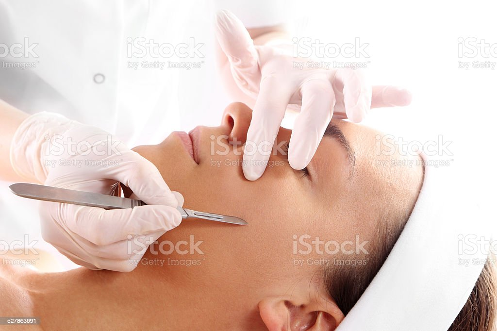 Cutting scars woman during treatment with dermatologist stock photo