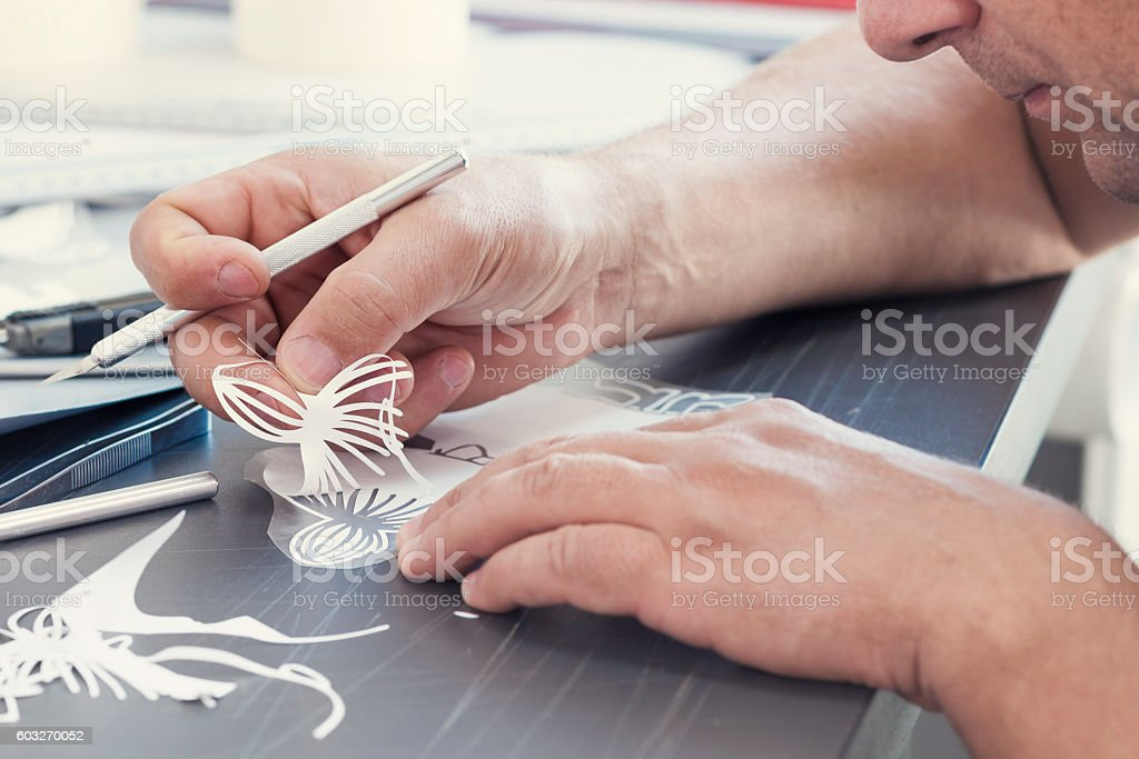 Cutting self-adhesive vinyl stock photo