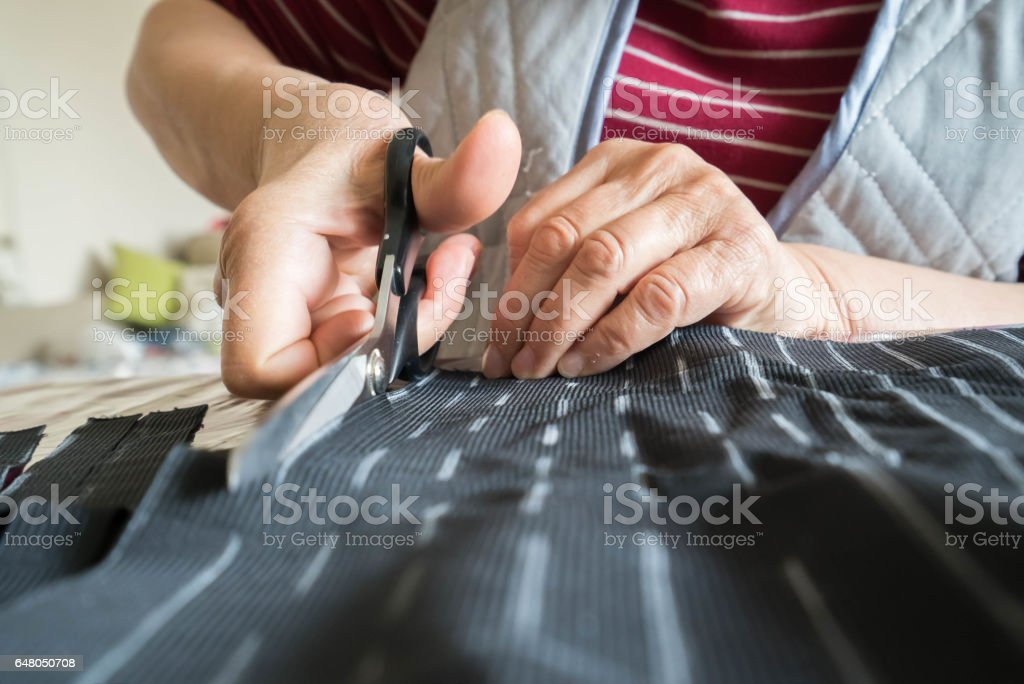 Cutting the cloth with scissors stock photo