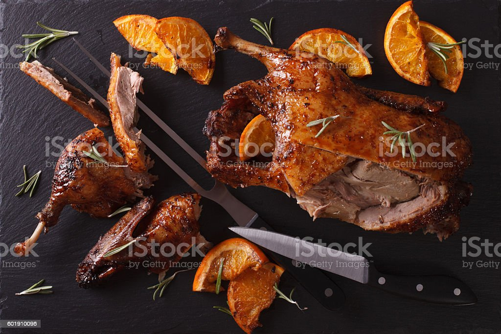 Cutting the roast duck and oranges on slate board. Horizontal stock photo