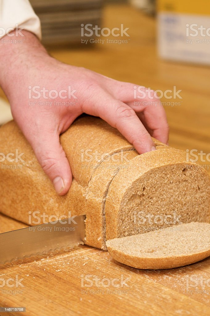 Cutting through bread royalty-free stock photo