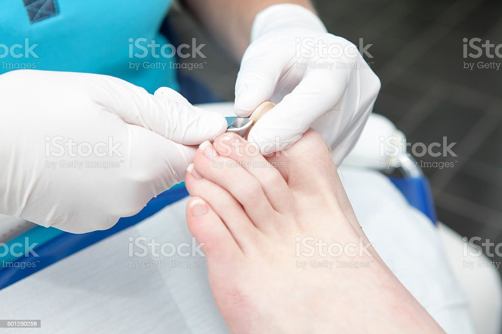 Cutting toe nails by pedicure stock photo