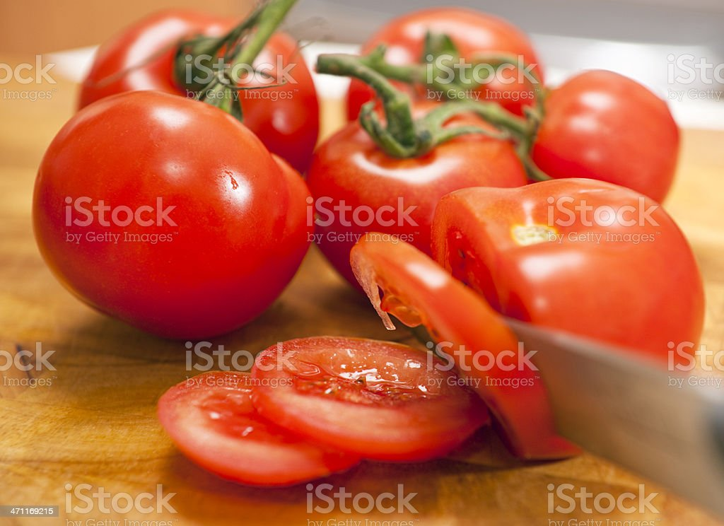 cutting tomatoes in kitchen stock photo
