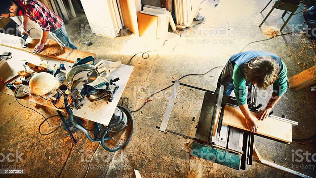 Cutting wood on a circular saw machine. stock photo