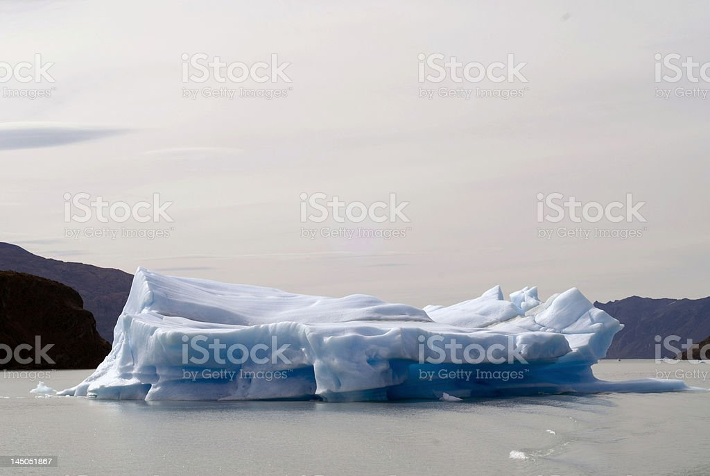 cyan Iceberg in red environment stock photo