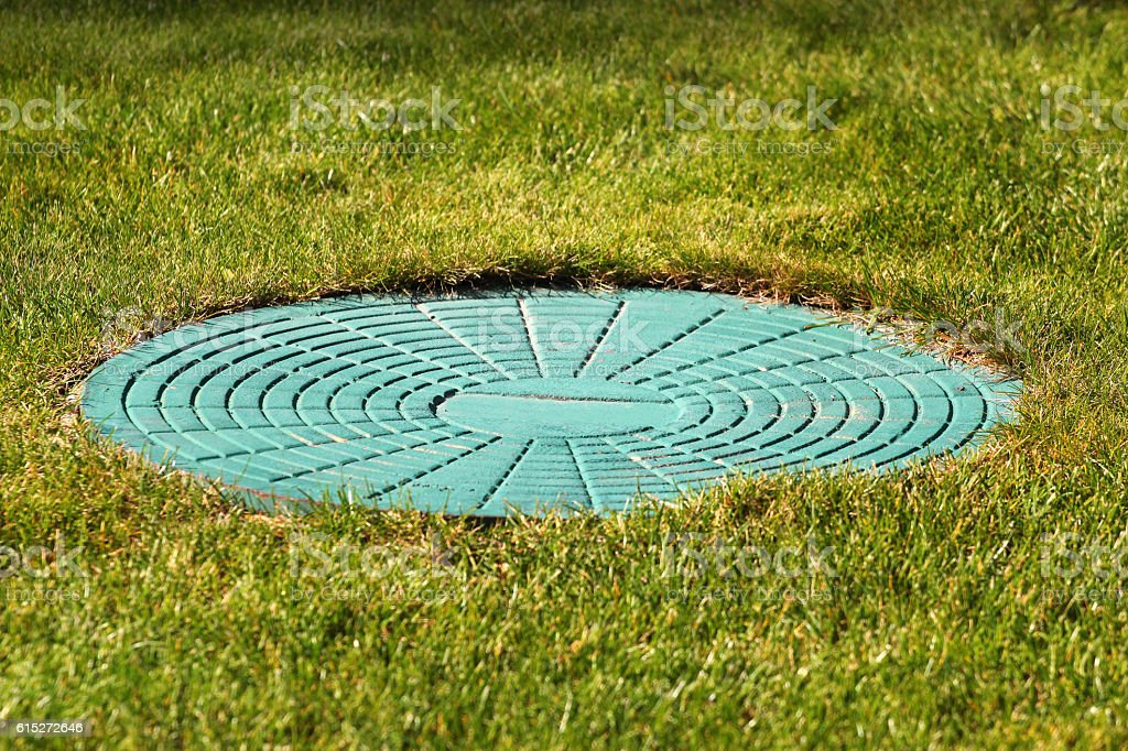 Cyan manhole cover in green grass stock photo