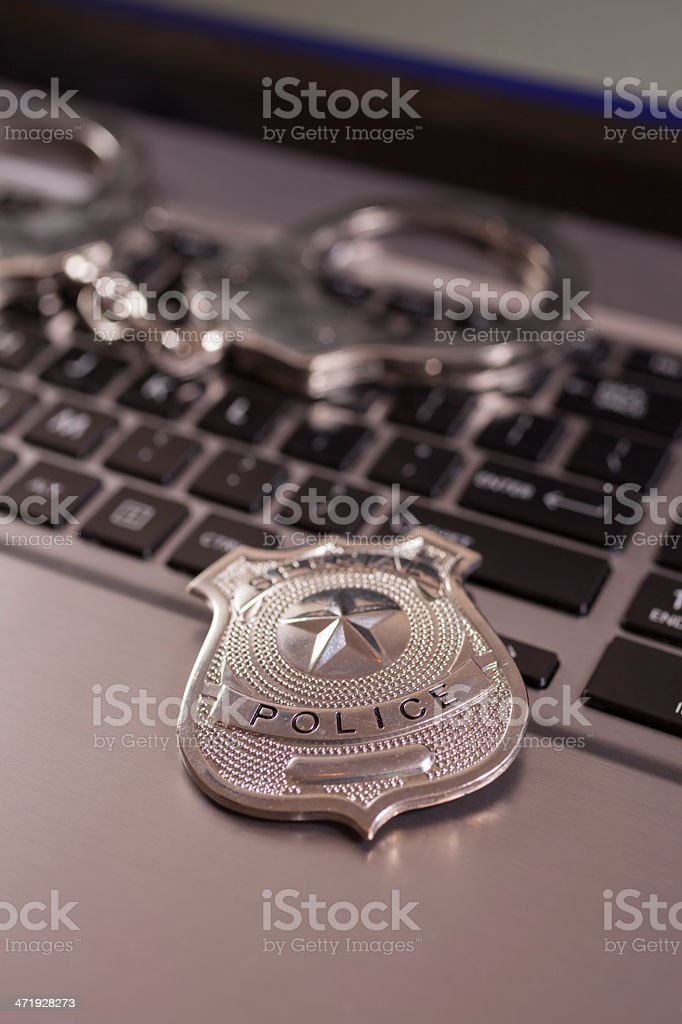 Cyber Crime: Handcuffs and police badge on laptop. stock photo
