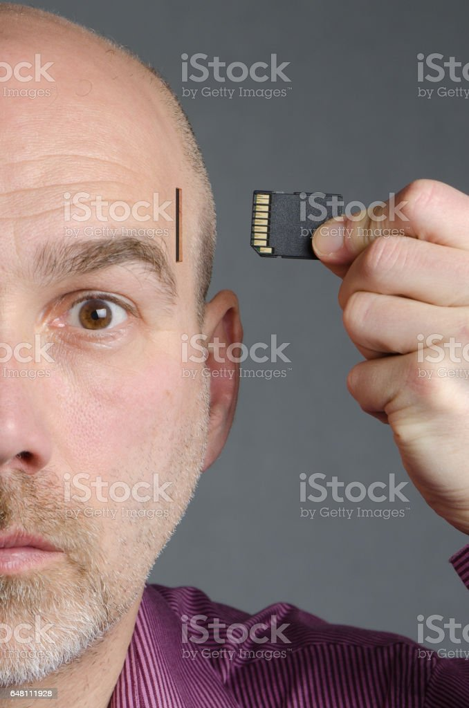 Close up on Cyborg Man inserting memory card on side of head