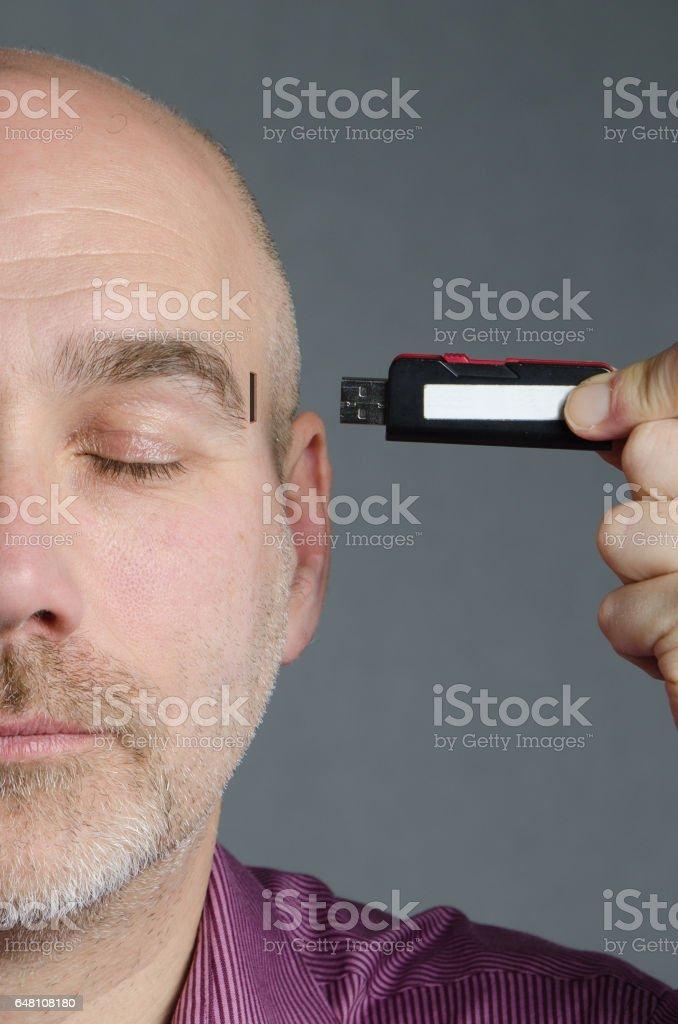 Close up on Cyborg Man inserting USB stick on side of head