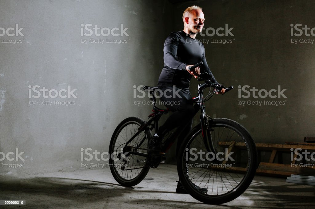 cycle man with bike indoors stock photo