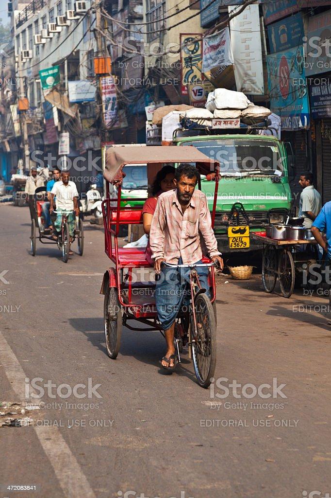 cycle rickshaw driver with passenger in Chawri Bazar, Delhi earl stock photo