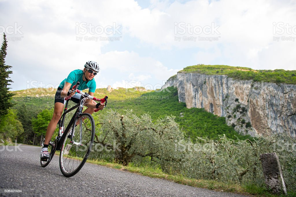 cycling downhill - woman with road bike in full speed stock photo