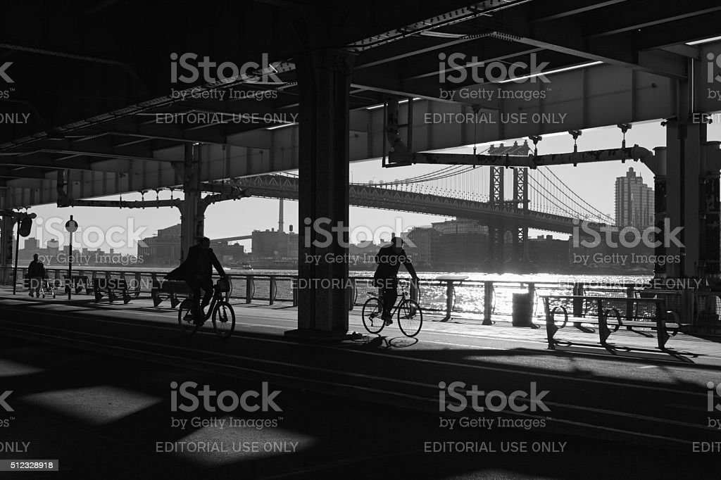 Cycling in shadows under the Manhattan Bridge NYC stock photo