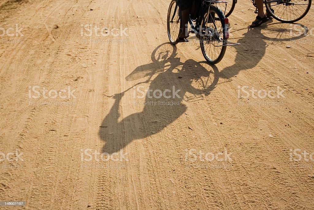 Cycling shadows on a dirt road in the sun royalty-free stock photo