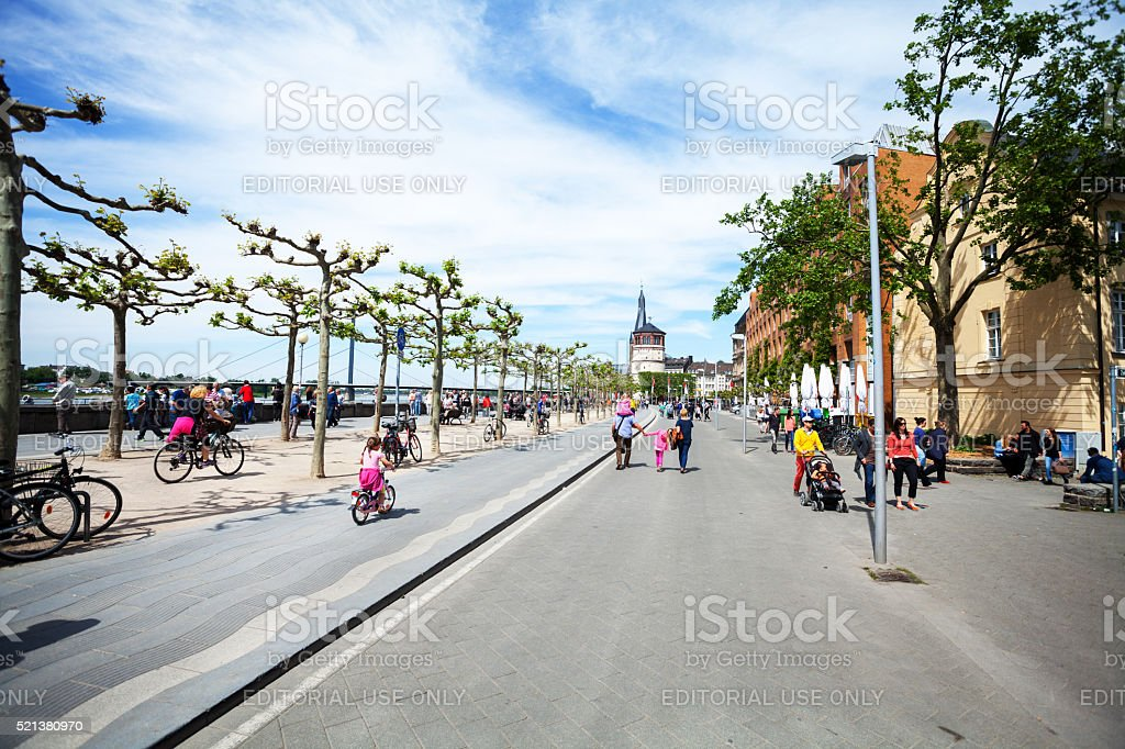 Cyclist and pedestrians on promenade at Rhine stock photo