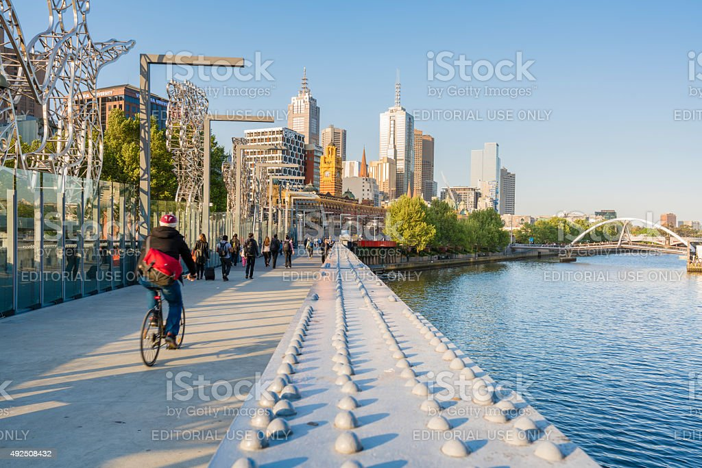 Cyclist and people walking across a bridge in downtown Melbourne stock photo