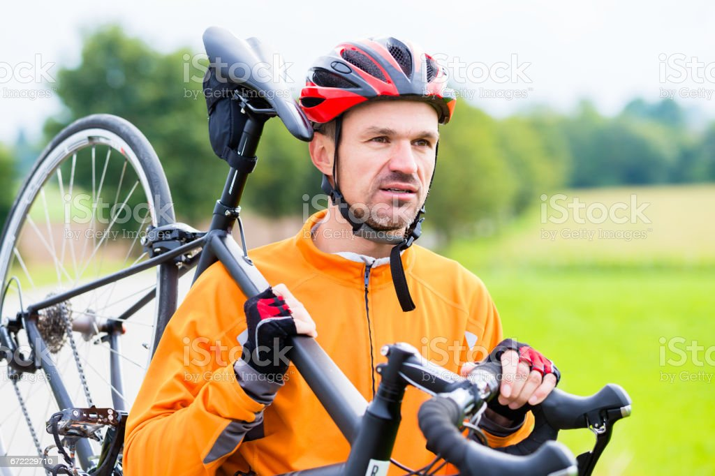 Cyclist carrying his bike over shoulder stock photo
