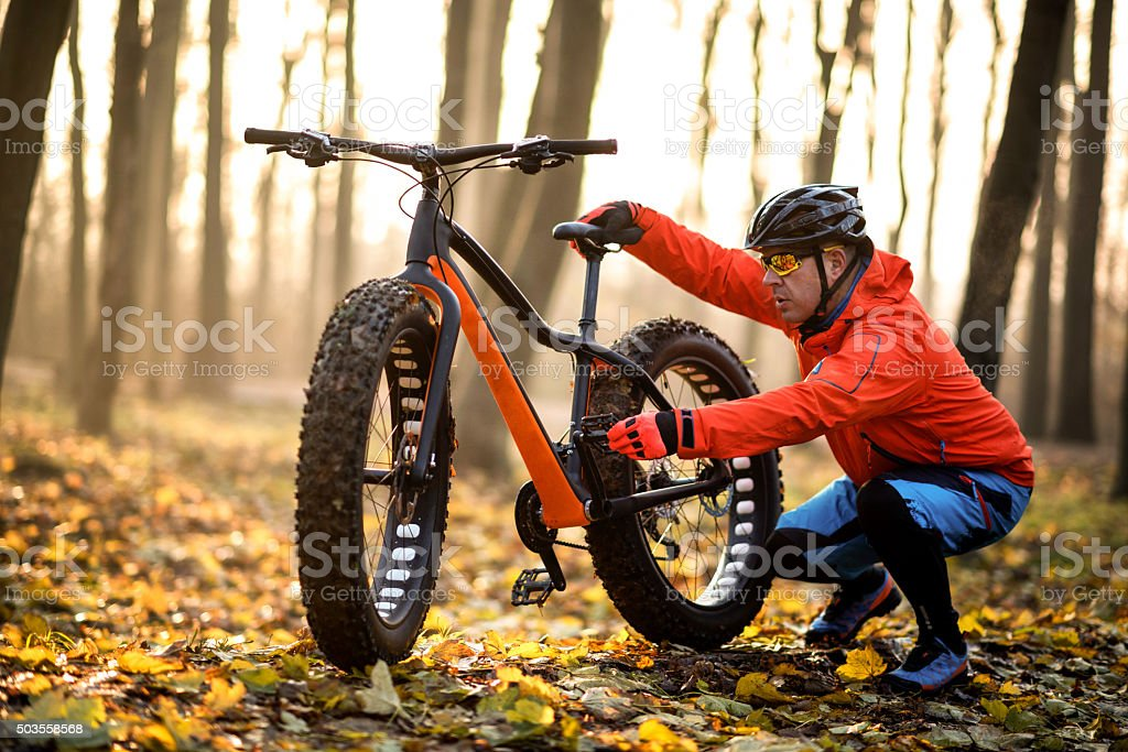 Cyclist checking fat bike pedal stock photo
