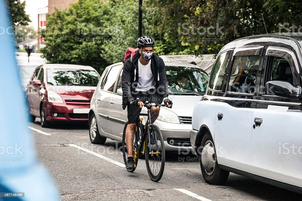 Cyclist commuter wearing a pollution-mask in Central London stock photo