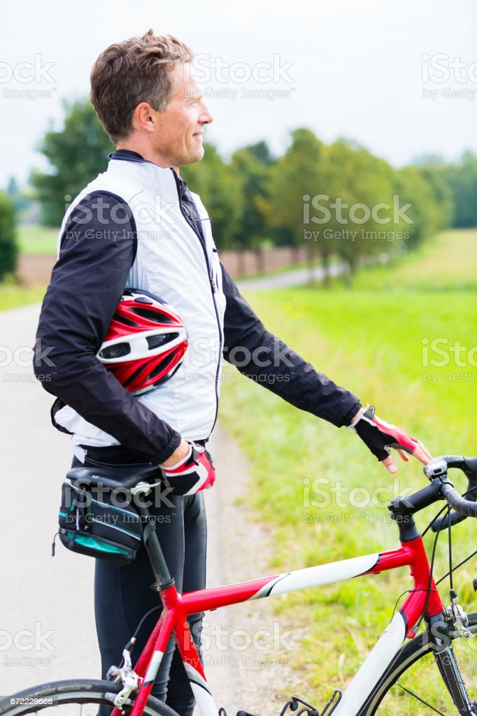 Cyclist, descended from his bike, has helmet in arm stock photo