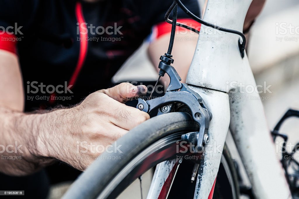 Cyclist fix the chain on his bicycle stock photo