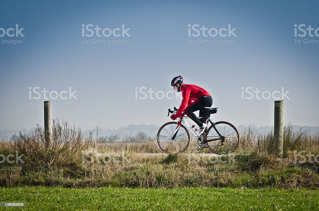 Cyclist in red on a rural bike path stock photo
