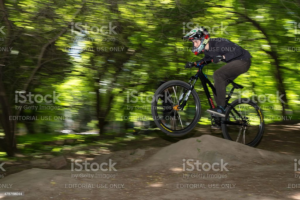 Cyclist jumps from ski jump stock photo