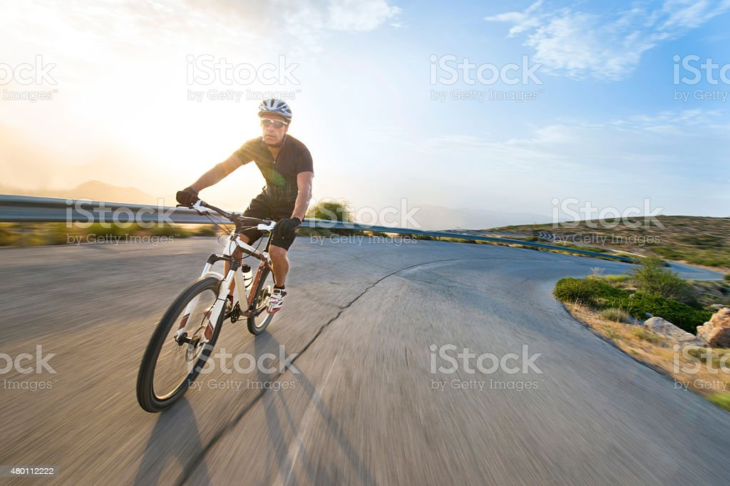 Cyclist man riding mountain bike in sunny day. stock photo