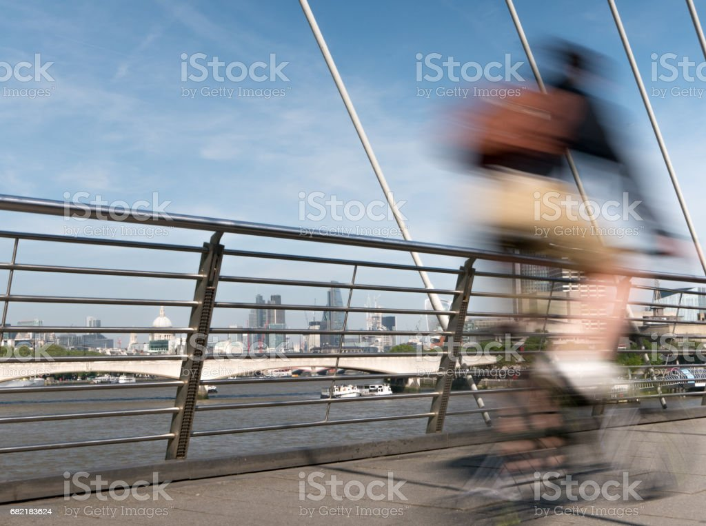 Cyclist on Golden Jubilee bridge in London. stock photo