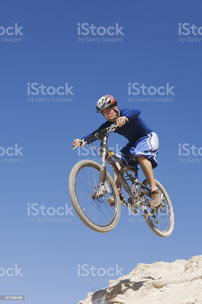 Cyclist on mountain bike jumping of a cliff stock photo
