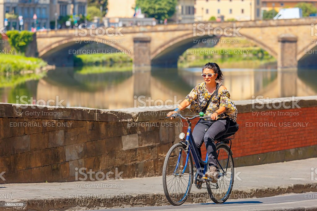 Cyclist on quay of river Arno in Florence, Italy stock photo
