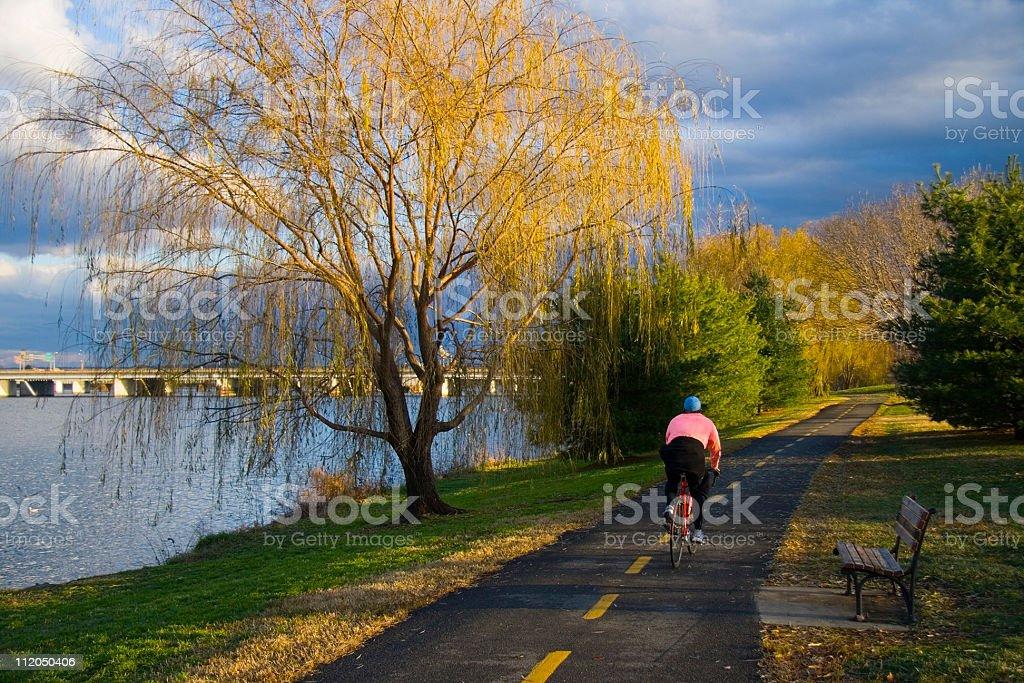 Cyclist pedaling down bike trail next to the Potomac at dawn royalty-free stock photo