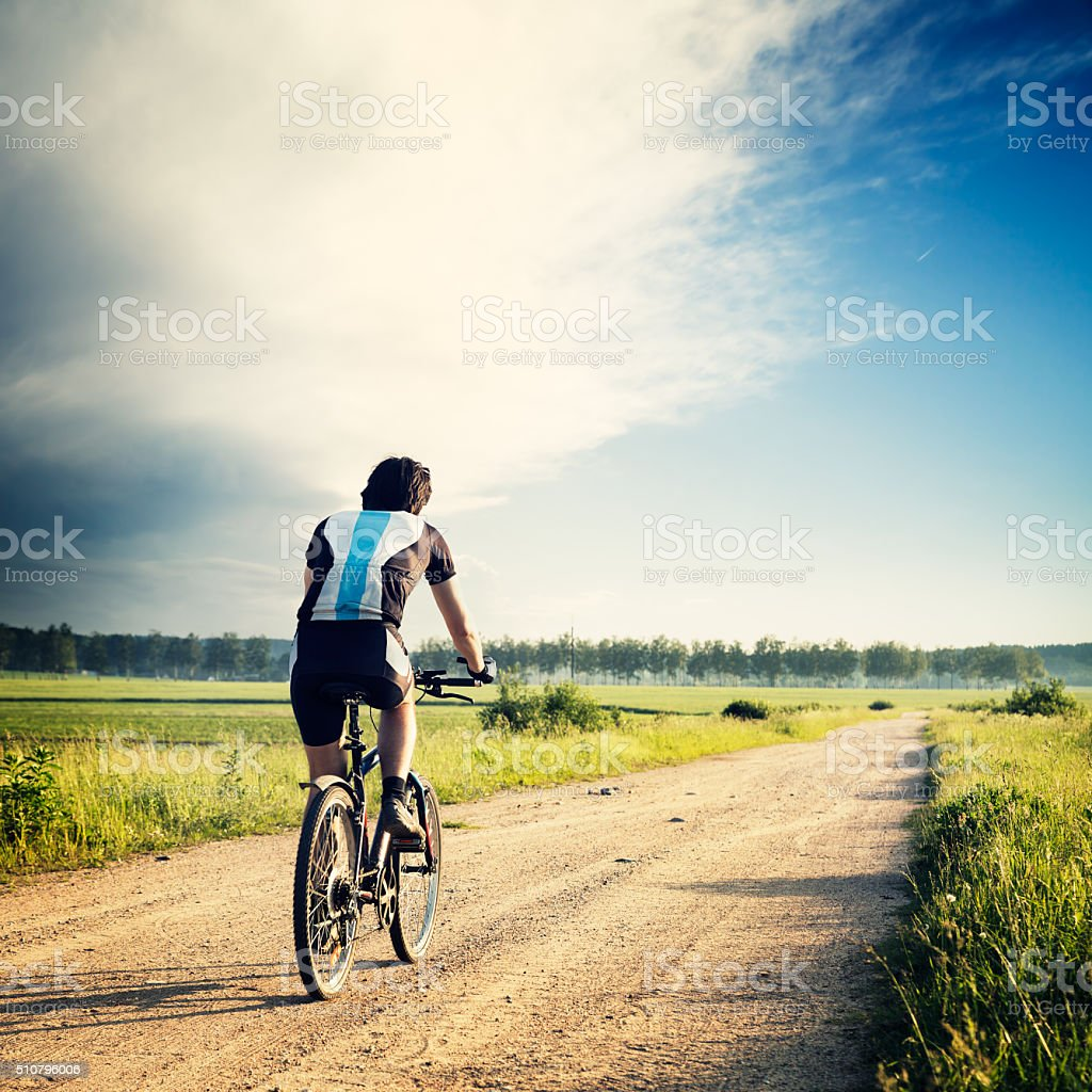 Cyclist Riding a Bike on the Country Road stock photo