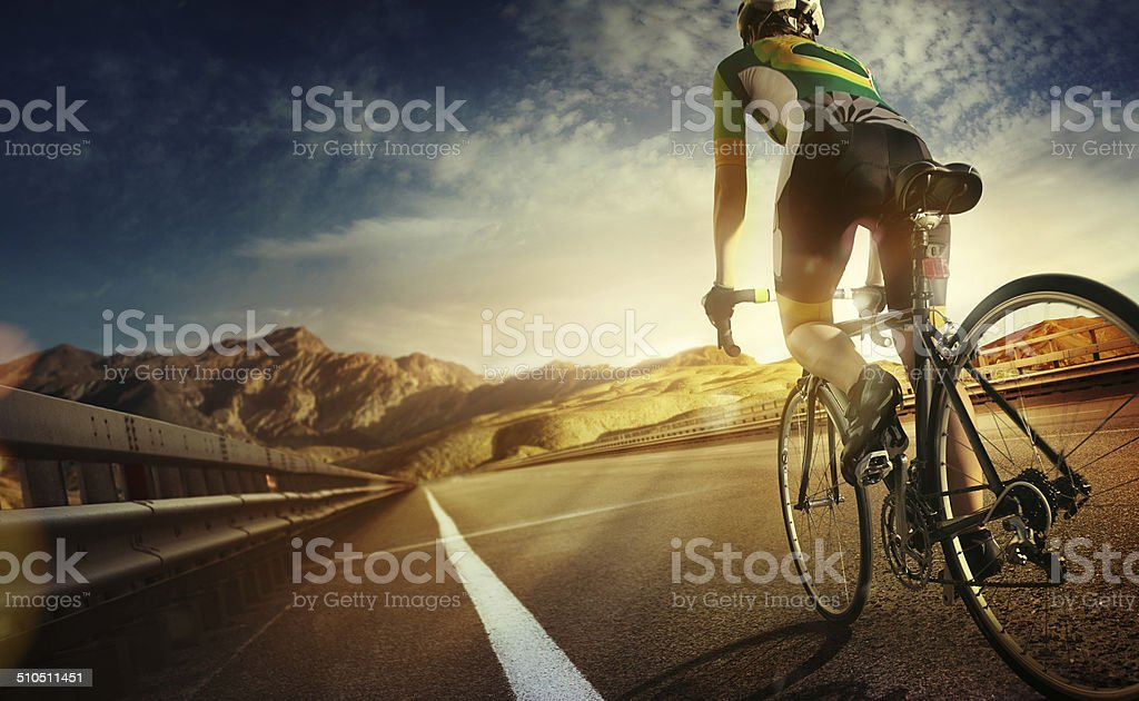 Cyclist riding a bike to the sunset on the highway stock photo
