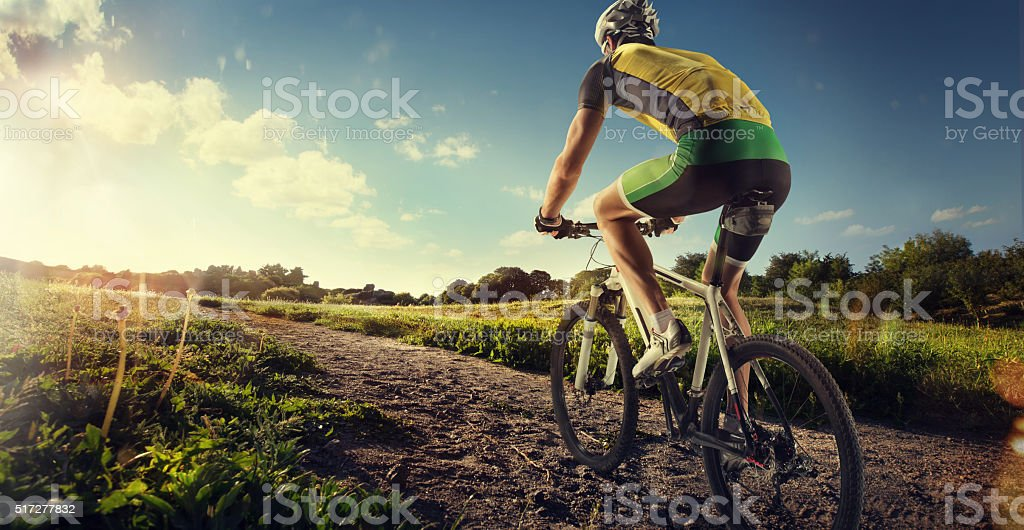 Cyclist riding a bike to the sunset on the ofroad stock photo