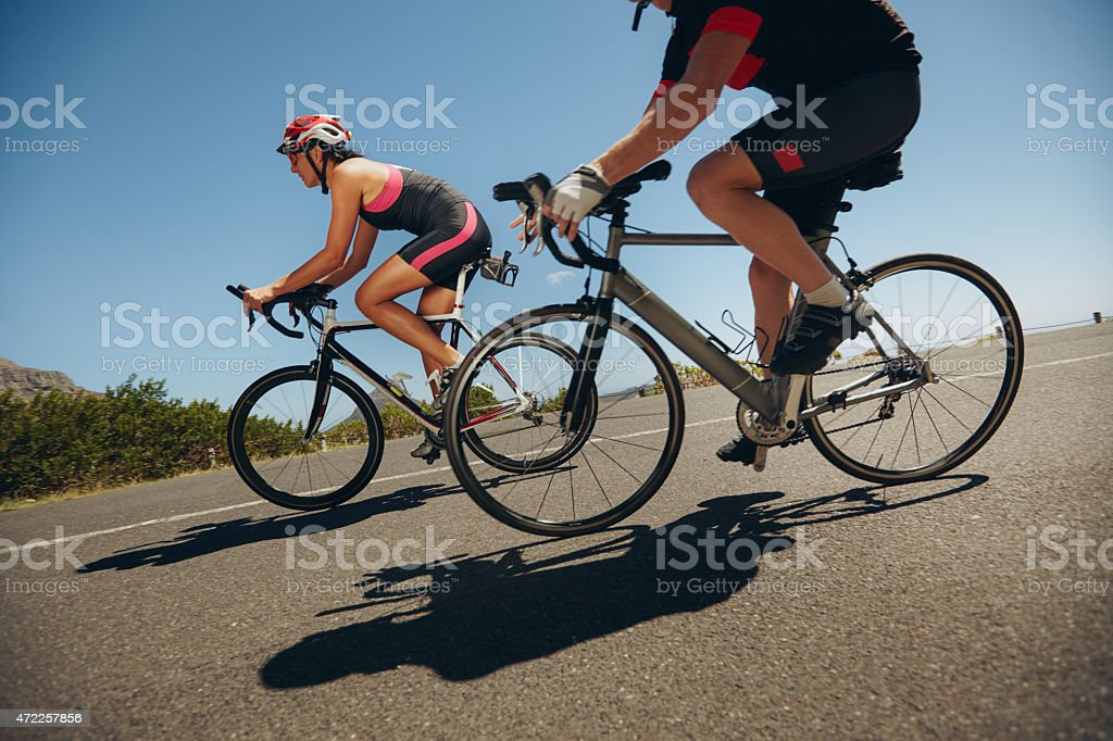 Cyclist riding bicycles down hill on country road stock photo