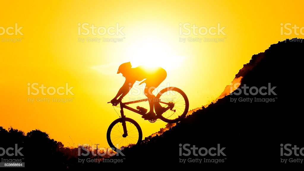 cyclist riding down hill stock photo
